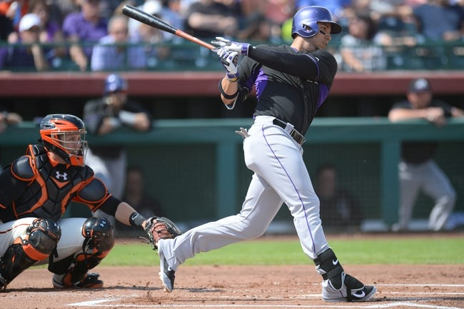 Mar 14, 2014; Scottsdale, AZ, USA; Colorado Rockies left fielder Carlos Gonzalez (5) follows through on a swing in the second inning against the San Francisco Giants at Scottsdale Stadium. Mandatory Credit: Joe Camporeale-USA TODAY Sports