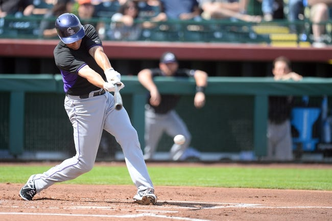 Mar 14, 2014; Scottsdale, AZ, USA; Colorado Rockies catcher Matt McBride (7) singles in the second inning against the San Francisco Giants at Scottsdale Stadium. Mandatory Credit: Joe Camporeale-USA TODAY Sports