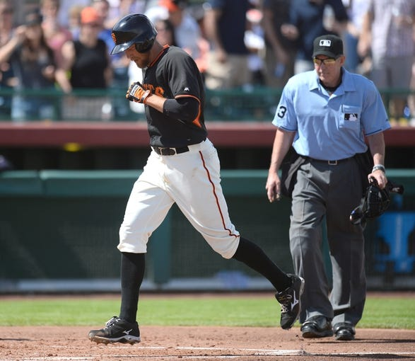 Mar 14, 2014; Scottsdale, AZ, USA; San Francisco Giants right fielder Hunter Pence (8) crosses home plate after hitting a solo home run in the second inning against the Colorado Rockies at Scottsdale Stadium. Mandatory Credit: Joe Camporeale-USA TODAY Sports