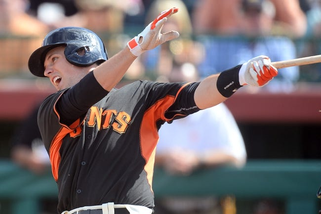 Mar 14, 2014; Scottsdale, AZ, USA; San Francisco Giants catcher Buster Posey (28) hits a single in the fifth inning against the Colorado Rockies at Scottsdale Stadium. Mandatory Credit: Joe Camporeale-USA TODAY Sports
