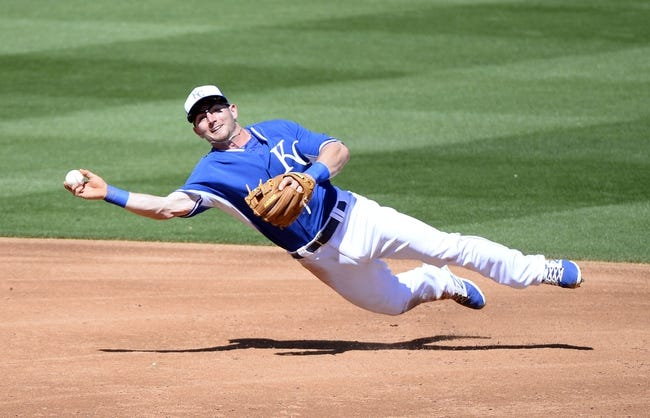Mar 15, 2014; Surprise, AZ, USA; Kansas City Royals second baseman Johnny Giavotella (9) throws to first during the third inning against the Chicago Cubs at Surprise Stadium. Mandatory Credit: Christopher Hanewinckel-USA TODAY Sports