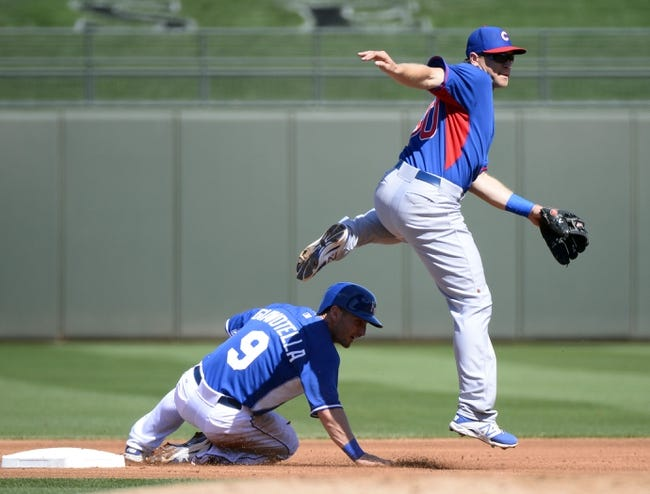 Mar 15, 2014; Surprise, AZ, USA; Chicago Cubs shortstop Chris Valaika (60) avoids contact with Kansas City Royals second baseman Johnny Giavotella (9) to complete a double play during the first inning  at Surprise Stadium. Mandatory Credit: Christopher Hanewinckel-USA TODAY Sports