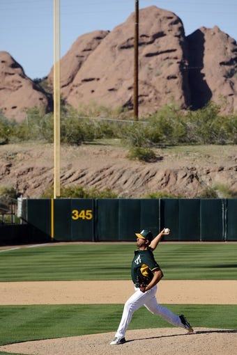 Mar 15, 2014; Phoenix, AZ, USA; Oakland Athletics relief pitcher Deryk Hooker (71) pitches against the Texas Rangers in the ninth inning at Phoenix Municipal Stadium. The Rangers won 16-15. Mandatory Credit: Joe Camporeale-USA TODAY Sports