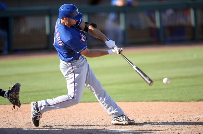 Mar 15, 2014; Phoenix, AZ, USA; Texas Rangers third baseman Kevin Kouzmanoff (6) swings at a pitch in the ninth inning at Phoenix Municipal Stadium. The Rangers won 16-15. Mandatory Credit: Joe Camporeale-USA TODAY Sports