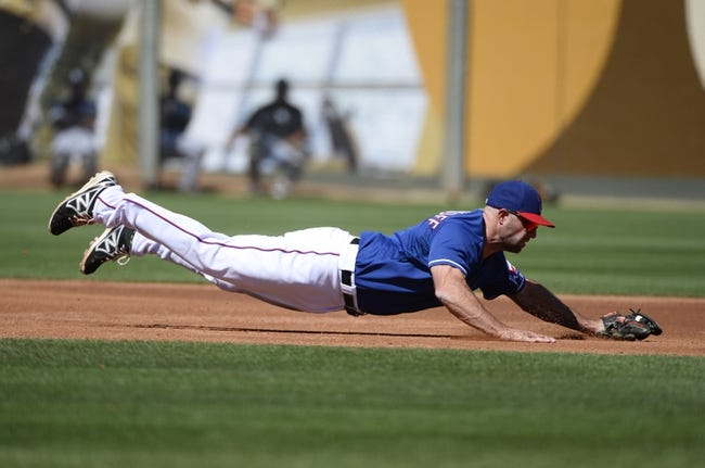 Mar 16, 2014; Surprise, AZ, USA; Texas Rangers third baseman Kevin Kouzmanoff (6) makes a diving stop during the third inning against the Chicago White Sox at Surprise Stadium. Mandatory Credit: Christopher Hanewinckel-USA TODAY Sports
