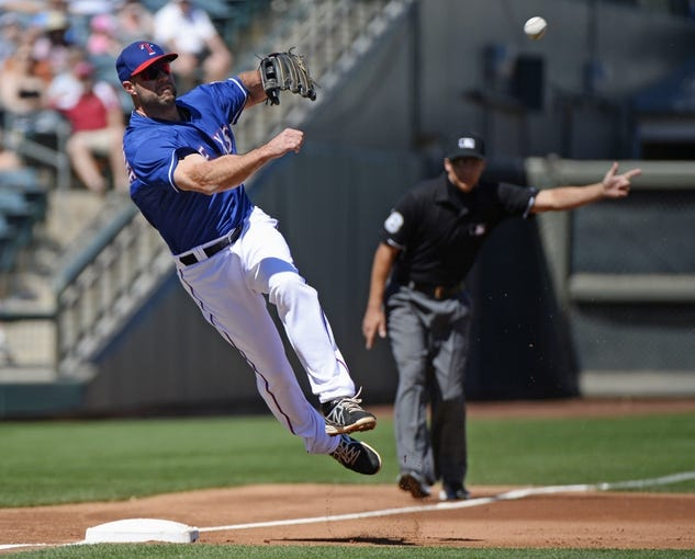 Mar 16, 2014; Surprise, AZ, USA; Texas Rangers third baseman Kevin Kouzmanoff (6) throws to first for an out  during the second inning against the Chicago White Sox at Surprise Stadium. Mandatory Credit: Christopher Hanewinckel-USA TODAY Sports