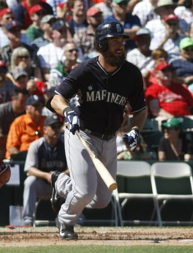 Mar 16, 2014; Tempe, AZ, USA; Seattle Mariners center fielder Dustin Ackley (13) hits an RBI single in the first inning against the Los Angeles Angels at Tempe Diablo Stadium. Mandatory Credit: Rick Scuteri-USA TODAY Sports