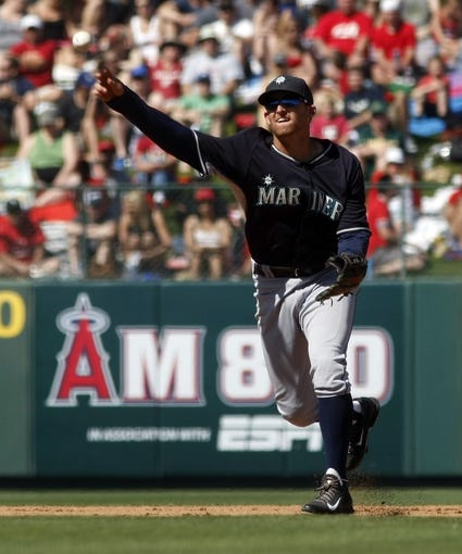 Mar 16, 2014; Tempe, AZ, USA; Seattle Mariners shortstop Brad Miller (5) makes the throw for the out against the Los Angeles Angels in the fourth inning at Tempe Diablo Stadium. Mandatory Credit: Rick Scuteri-USA TODAY Sports