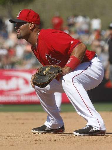 Mar 16, 2014; Tempe, AZ, USA; Los Angeles Angels first baseman Albert Pujols (5) in the fourth inning against the Seattle Mariners at Tempe Diablo Stadium. Mandatory Credit: Rick Scuteri-USA TODAY Sports