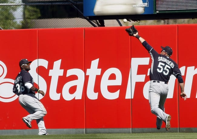 Mar 16, 2014; Tempe, AZ, USA; Seattle Mariners center fielder Michael Saunders (55) makes the running catch in the fifth inning against the Los Angeles Angels at Tempe Diablo Stadium. Mandatory Credit: Rick Scuteri-USA TODAY Sports