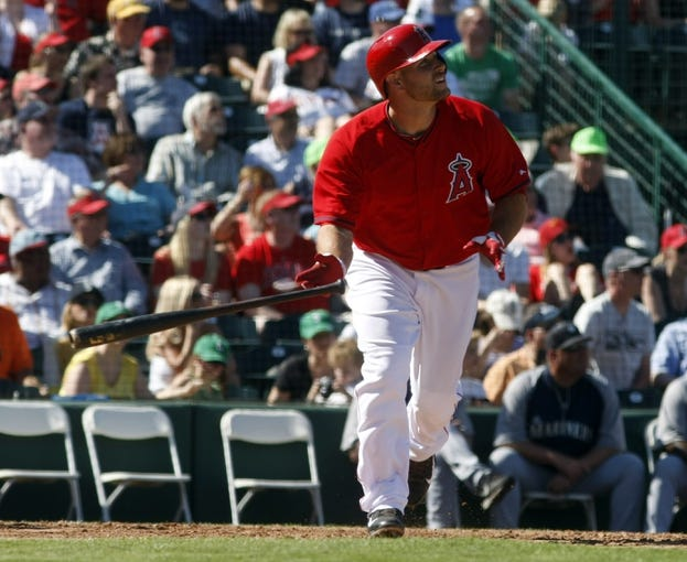 Mar 16, 2014; Tempe, AZ, USA; Los Angeles Angels catcher Chris Iannetta (17) hits an RBI sacrifice fly against the Seattle Mariners in the fifth inning at Tempe Diablo Stadium. Mandatory Credit: Rick Scuteri-USA TODAY Sports