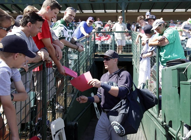 Mar 16, 2014; Tempe, AZ, USA; Seattle Mariners first baseman Logan Morrison (20) signs autographs before a game against the Los Angeles Angels at Tempe Diablo Stadium. Mandatory Credit: Rick Scuteri-USA TODAY Sports