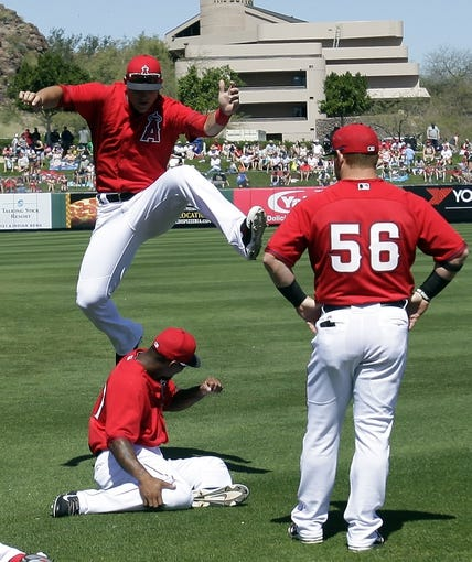 Mar 16, 2014; Tempe, AZ, USA; Los Angeles Angels center fielder Mike Trout (27) jumps over Howie Kendrick (47) while warming up before a game against the Seattle Mariners at Tempe Diablo Stadium. Mandatory Credit: Rick Scuteri-USA TODAY Sports