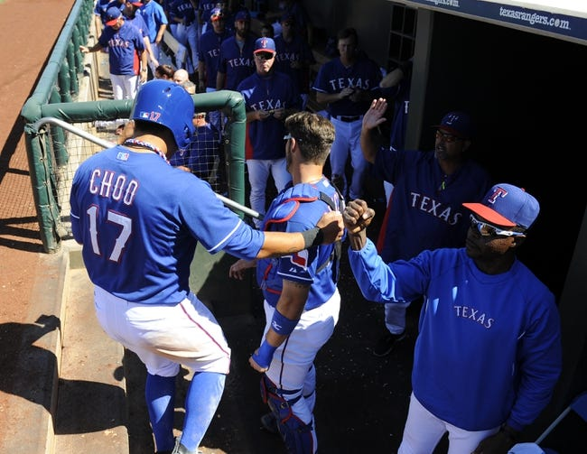 Mar 16, 2014; Surprise, AZ, USA; Texas Rangers designated hitter Shin-Soo Choo (17) is congratulated by teammates after scoring during the third inning at Surprise Stadium. Mandatory Credit: Christopher Hanewinckel-USA TODAY Sports