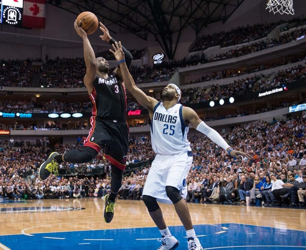 Feb 18, 2014; Dallas, TX, USA; Miami Heat shooting guard Dwyane Wade (3) shoots over Dallas Mavericks shooting guard Vince Carter (25) during the game at the American Airlines Center. The Heat defeated the Mavericks  117-106. Mandatory Credit: Jerome Miron-USA TODAY Sports