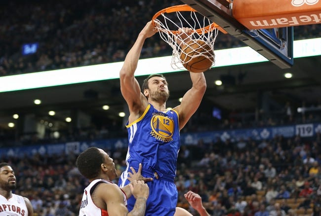 Mar 2, 2014; Toronto, Ontario, CAN; Golden State Warriors center Andrew Bogut (12) dunks against the Toronto Raptors at Air Canada Centre. The Raptors beat the Warriors 104-98. Mandatory Credit: Tom Szczerbowski-USA TODAY Sports