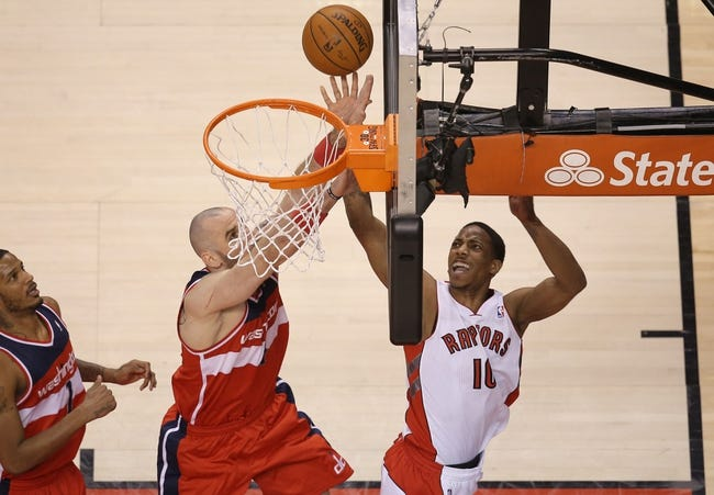Feb 27, 2014; Toronto, Ontario, CAN; Toronto Raptors guard DeMar DeRozan (10) is fouled as he goes to the basket against Washington Wizards center Marcin Gortat (4) at Air Canada Centre. The Wizards beat the Raptors 134-129 in triple overtime. Mandatory Credit: Tom Szczerbowski-USA TODAY Sports