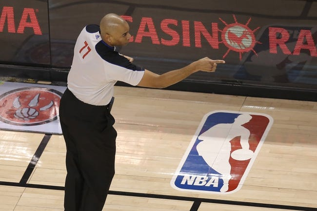 Feb 27, 2014; Toronto, Ontario, CAN; NBA official Karl Lane (77) makes an offensive foul call against the Washington Wizards during their game against the Toronto Raptors at Air Canada Centre. The Wizards beat the Raptors 134-129 in triple overtime. Mandatory Credit: Tom Szczerbowski-USA TODAY Sports
