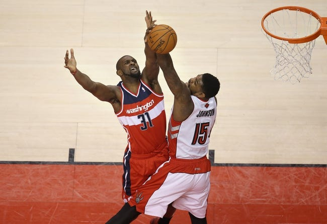 Feb 27, 2014; Toronto, Ontario, CAN; Washington Wizards forward Chris Singleton (31) is fouled by Toronto Raptors forward Amir Johnson (15) as he goes to the basket at Air Canada Centre. The Wizards beat the Raptors 134-129 in triple overtime. Mandatory Credit: Tom Szczerbowski-USA TODAY Sports