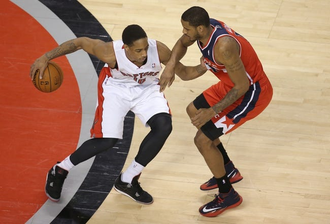Feb 27, 2014; Toronto, Ontario, CAN; Toronto Raptors guard DeMar DeRozan (10) is guarded by Washington Wizards forward Trevor Ariza (1) as he dribbles at Air Canada Centre. The Wizards beat the Raptors 134-129 in triple overtime. Mandatory Credit: Tom Szczerbowski-USA TODAY Sports