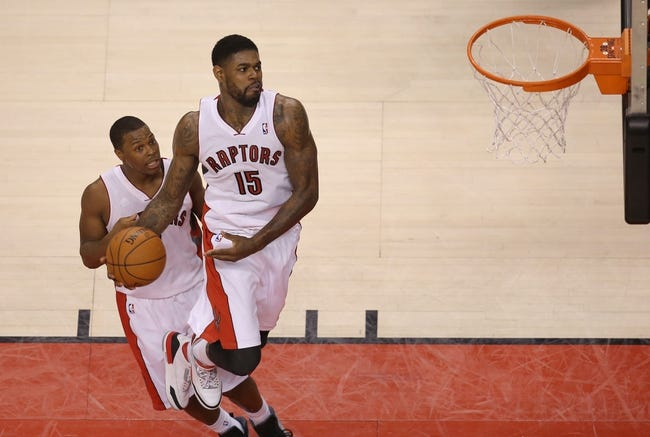 Feb 27, 2014; Toronto, Ontario, CAN; Toronto Raptors forward Amir Johnson (15) jumps as he dunks while point guard Kyle Lowry (7) watches against the Washington Wizards at Air Canada Centre. The Wizards beat the Raptors 134-129 in triple overtime. Mandatory Credit: Tom Szczerbowski-USA TODAY Sports