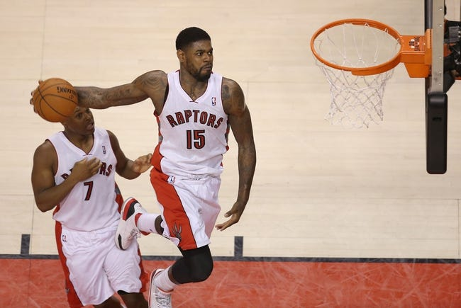 Feb 27, 2014; Toronto, Ontario, CAN; Toronto Raptors forward Amir Johnson (15) dunks as point guard Kyle Lowry (7) watches against the Washington Wizards at Air Canada Centre. The Wizards beat the Raptors 134-129 in triple overtime. Mandatory Credit: Tom Szczerbowski-USA TODAY Sports
