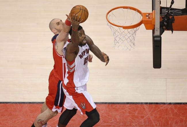 Feb 27, 2014; Toronto, Ontario, CAN; Toronto Raptors forward Amir Johnson (15) is fouled by Washington Wizards center Marcin Gortat (4) as he goes to the basket at Air Canada Centre. The Wizards beat the Raptors 134-129 in triple overtime. Mandatory Credit: Tom Szczerbowski-USA TODAY Sports
