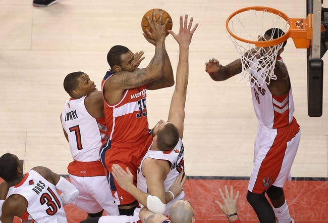 Feb 27, 2014; Toronto, Ontario, CAN; Washington Wizards forward Trevor Booker (35) is fouled as he goes to the basket by Toronto Raptors point guard Kyle Lowry (7) as center Jonas Valanciunas (17) tries to defend at Air Canada Centre. The Wizards beat the Raptors 134-129 in triple overtime. Mandatory Credit: Tom Szczerbowski-USA TODAY Sports