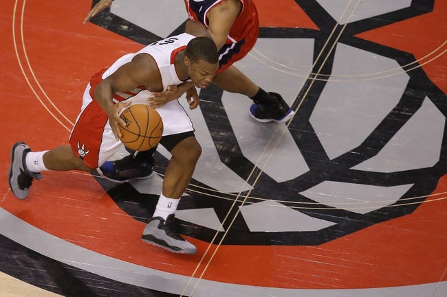 Feb 27, 2014; Toronto, Ontario, CAN; Toronto Raptors point guard Kyle Lowry (7) dribbles up the court as Washington Wizards guard Andre Miller (24) plays defense at Air Canada Centre. The Wizards beat the Raptors 134-129 in triple overtime. Mandatory Credit: Tom Szczerbowski-USA TODAY Sports
