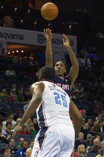 Mar 17, 2014; Charlotte, NC, USA; Atlanta Hawks guard Jeff Teague (0) shoots the ball during the first half against the Charlotte Bobcats at Time Warner Cable Arena. Mandatory Credit: Jeremy Brevard-USA TODAY Sports