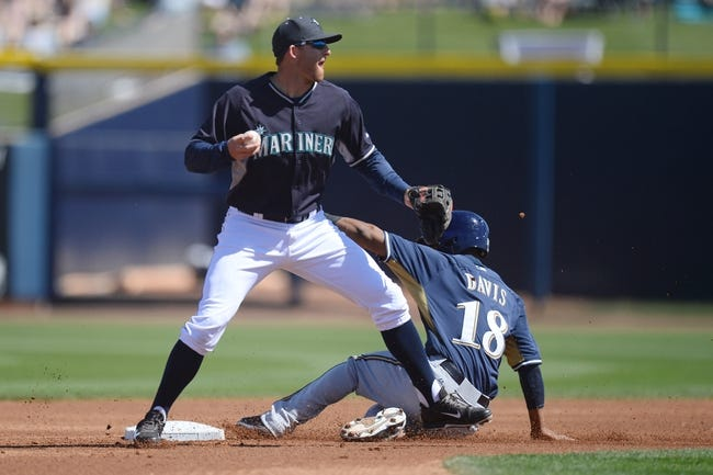 Mar 19, 2014; Peoria, AZ, USA; Milwaukee Brewers left fielder Khris Davis (18) attempts to break up a double play by Seattle Mariners shortstop Brad Miller (5) at Peoria Sports Complex. The Brewers won 9-7. Mandatory Credit: Joe Camporeale-USA TODAY Sports