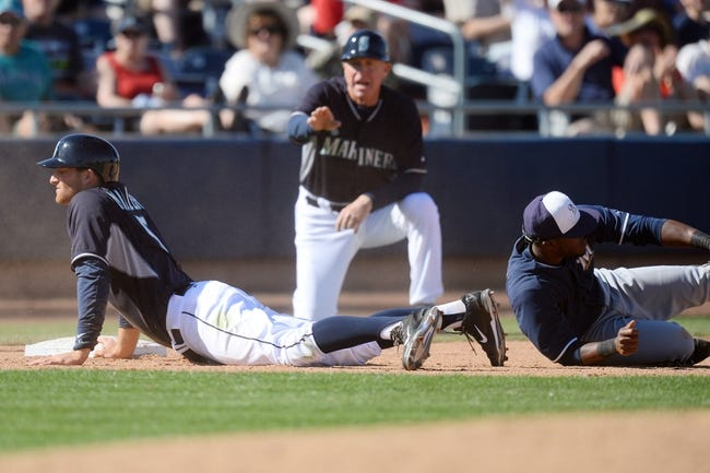 Mar 19, 2014; Peoria, AZ, USA; Seattle Mariners shortstop Brad Miller (5) slides into third base after hitting a triple against the Milwaukee Brewers at Peoria Sports Complex. The Brewers won 9-7. Mandatory Credit: Joe Camporeale-USA TODAY Sports