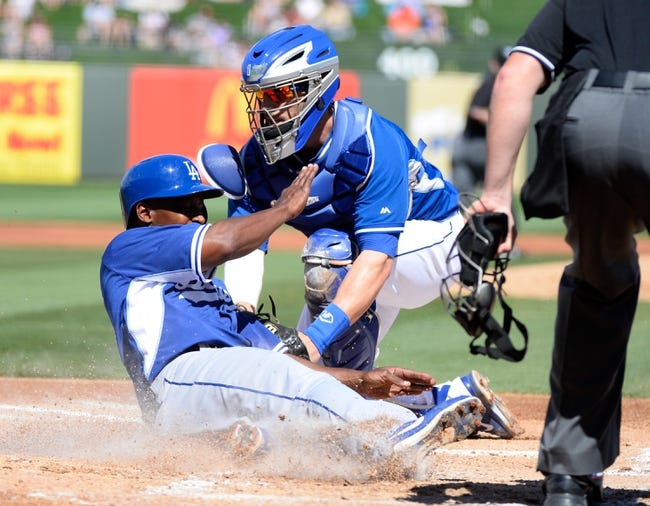 Mar 11, 2014; Surprise, AZ, USA;  Los Angeles Dodgers shortstop Chone Figgins (18) is tagged out by Kansas City Royals catcher Brett Hayes (12) during the third inning at Surprise Stadium. Mandatory Credit: Christopher Hanewinckel-USA TODAY Sports