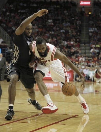Mar 20, 2014; Houston, TX, USA; Houston Rockets guard James Harden (13) drives to the basket against Minnesota Timberwolves forward Luc Richard Mbah a Moute (12) during the second quarter at Toyota Center. Mandatory Credit: Andrew Richardson-USA TODAY Sports
