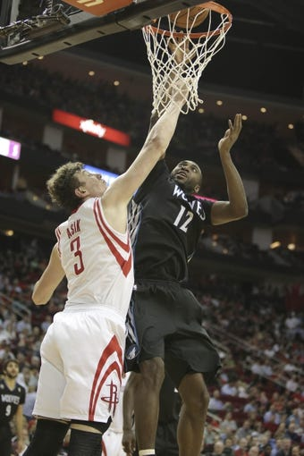 Mar 20, 2014; Houston, TX, USA; Minnesota Timberwolves forward Luc Richard Mbah a Moute (12) shoots the ball over Houston Rockets center Omer Asik (3) during the third quarter at Toyota Center. Mandatory Credit: Andrew Richardson-USA TODAY Sports