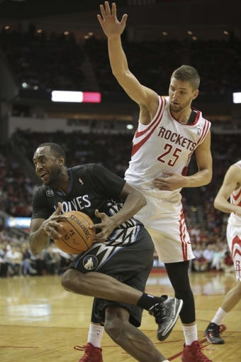 Mar 20, 2014; Houston, TX, USA; Minnesota Timberwolves forward Luc Richard Mbah a Moute (12) drives to the basket against Houston Rockets forward Chandler Parsons (25) during the fourth quarter at Toyota Center. Mandatory Credit: Andrew Richardson-USA TODAY Sports
