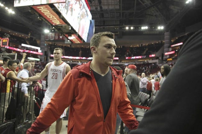 Mar 20, 2014; Houston, TX, USA; Texas A&M quarterback Johnny Manziel shake hands with fans following the fourth quarter of the game between the Minnesota Timberwolves and the Houston Rockets at Toyota Center. Mandatory Credit: Andrew Richardson-USA TODAY Sports