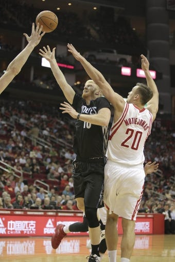 Mar 20, 2014; Houston, TX, USA; Minnesota Timberwolves forward Chase Budinger (10) shoots the ball over Houston Rockets forward Donatas Motiejunas (20) during the fourth quarter at Toyota Center. Mandatory Credit: Andrew Richardson-USA TODAY Sports