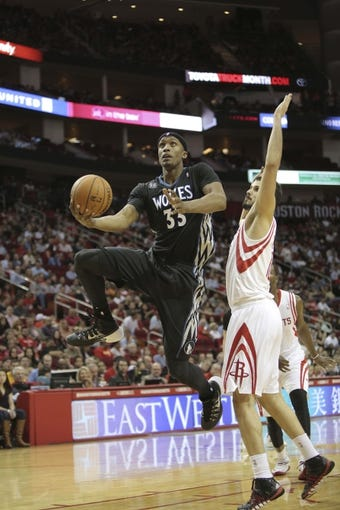 Mar 20, 2014; Houston, TX, USA; Minnesota Timberwolves forward Dante Cunningham (33) shoots the ball over Houston Rockets forward Omri Casspi (18) during the fourth quarter at Toyota Center. Mandatory Credit: Andrew Richardson-USA TODAY Sports