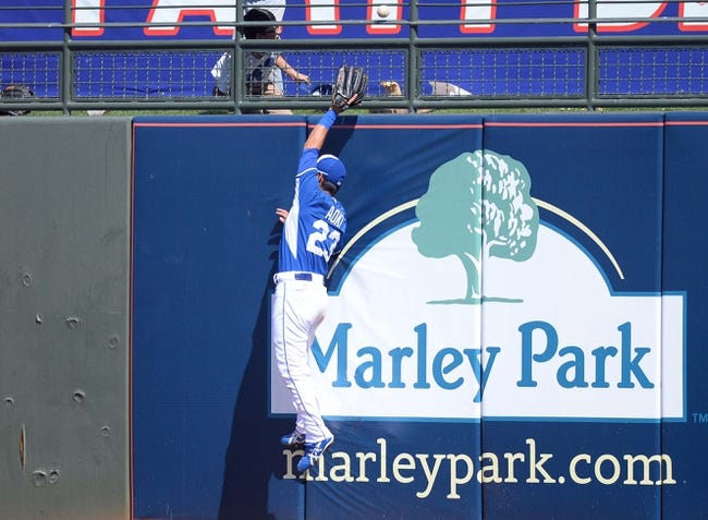Mar 22, 2014; Surprise, AZ, USA; Kansas City Royals right fielder Norichika Aoki (23) is unable to make a catch against the wall against the Texas Rangers at Surprise Stadium. The Royals won 8-4. Mandatory Credit: Joe Camporeale-USA TODAY Sports