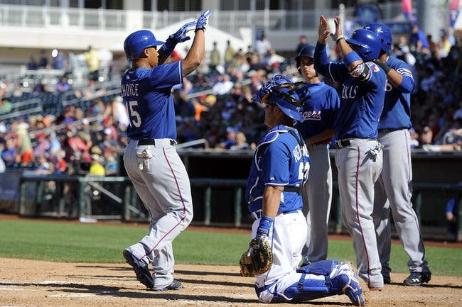 Mar 22, 2014; Surprise, AZ, USA; Texas Rangers center fielder Michael Choice (15) is high-rived by teammates after hitting a home run in the eighth inning against the Kansas City Royals at Surprise Stadium. The Royals won 8-4. Mandatory Credit: Joe Camporeale-USA TODAY Sports