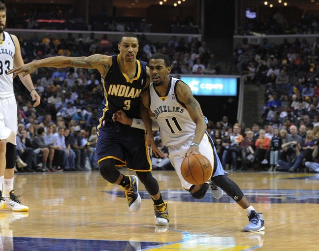 Mar 22, 2014; Memphis, TN, USA; Memphis Grizzlies guard Mike Conley (11) drives to the basket against Indiana Pacers guard George Hill (3) during the game at FedExForum. Memphis Grizzlies defeat the Indiana Pacers 82 - 71. Mandatory Credit: Justin Ford-USA TODAY Sports