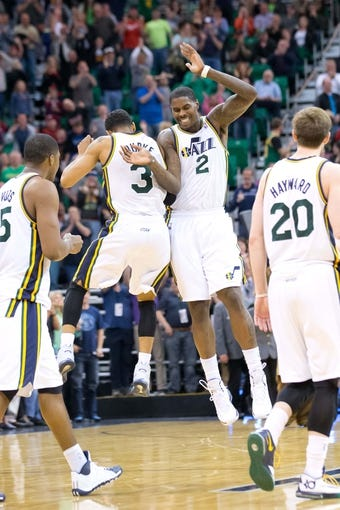 Mar 22, 2014; Salt Lake City, UT, USA; Utah Jazz forward Marvin Williams (2) and guard Trey Burke (3) react to Burke's go-ahead 3-point basket with 1.6 seconds remaining in the second half against the Orlando Magic at EnergySolutions Arena. The Jazz won 89-88. Mandatory Credit: Russ Isabella-USA TODAY Sports