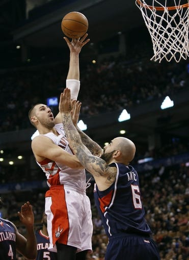 Mar 23, 2014; Toronto, Ontario, CAN; Toronto Raptors center Jonas Valanciunas (17) goes to make a basket as Atlanta Hawks center Pero Antic (6) defends during the first half at the Air Canada Centre. Mandatory Credit: John E. Sokolowski-USA TODAY Sports