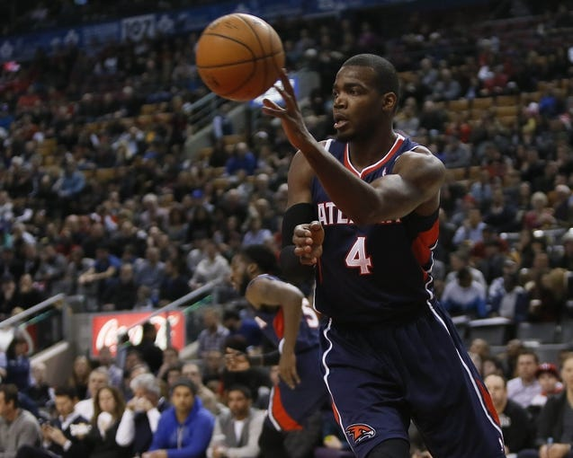 Mar 23, 2014; Toronto, Ontario, CAN; Atlanta Hawks forward Paul Millsap (4) passes the ball against the Toronto Raptors during the first half at the Air Canada Centre. Mandatory Credit: John E. Sokolowski-USA TODAY Sports