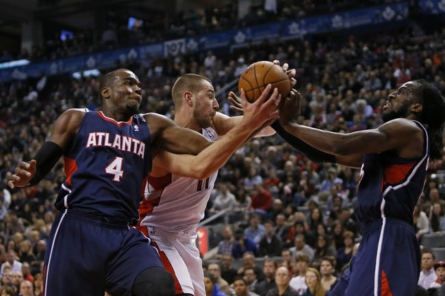 Mar 23, 2014; Toronto, Ontario, CAN; Toronto Raptors center Jonas Valanciunas (17) battles for the ball with Atlanta Hawks forward Paul Millsap (4) and forward DeMarre Carroll (5) during the first half at the Air Canada Centre. Mandatory Credit: John E. Sokolowski-USA TODAY Sports