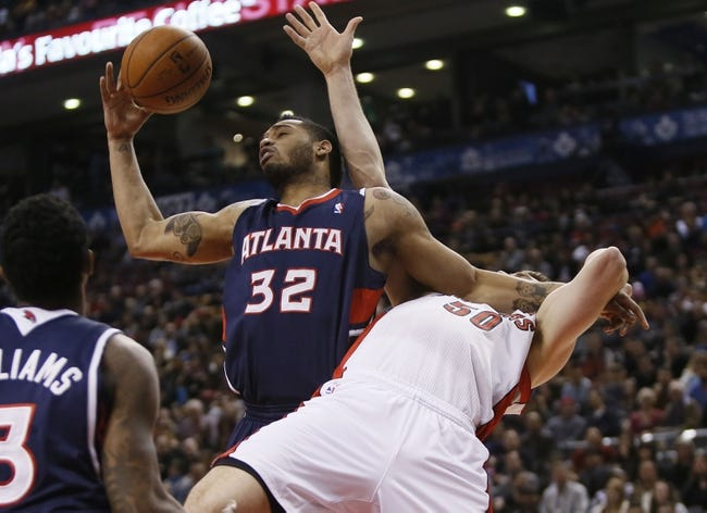 Mar 23, 2014; Toronto, Ontario, CAN; Atlanta Hawks forward Mike Scott (32) battles Toronto Raptors forward Tyler Hansbrough (50) for a rebound during the first half at the Air Canada Centre. Mandatory Credit: John E. Sokolowski-USA TODAY Sports