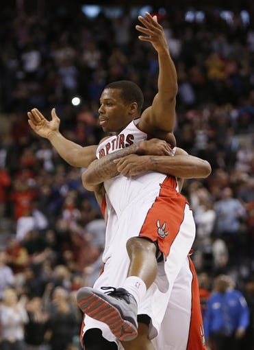 Mar 23, 2014; Toronto, Ontario, CAN; Toronto Raptors guard Kyle Lowry (left) gets hugged by guard DeMar DeRozan (right) after a win over the Atlanta Hawks at the Air Canada Centre. Toronto defeated Atlanta 96-86. Mandatory Credit: John E. Sokolowski-USA TODAY Sports