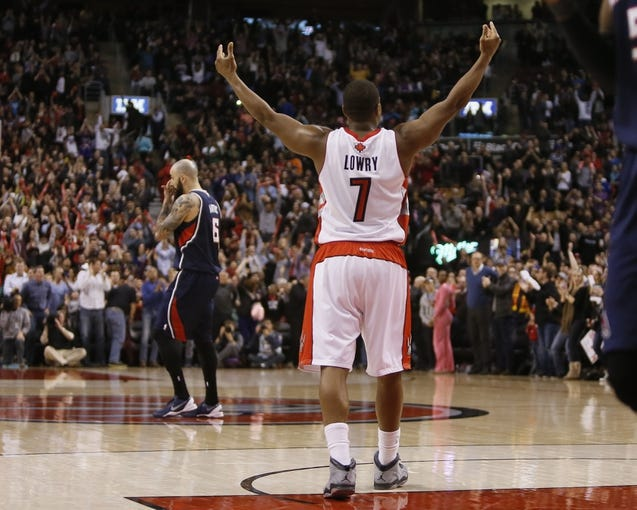 Mar 23, 2014; Toronto, Ontario, CAN; Toronto Raptors guard Kyle Lowry (7) celebrates a win as Atlanta Hawks center Pero Antic (6) walks off the court at the Air Canada Centre. Toronto defeated Atlanta 96-86. Mandatory Credit: John E. Sokolowski-USA TODAY Sports