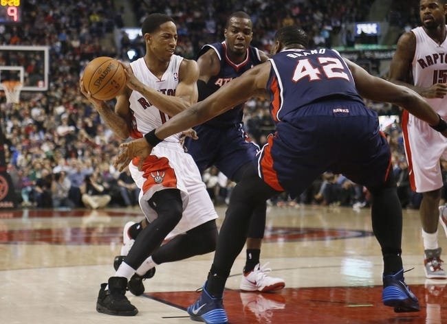 Mar 23, 2014; Toronto, Ontario, CAN; Toronto Raptors guard DeMar DeRozan (10) tries to get by Atlanta Hawks forward Elton Brand (42) and forward Paul Millsap (4) during the first half at the Air Canada Centre. Mandatory Credit: John E. Sokolowski-USA TODAY Sports